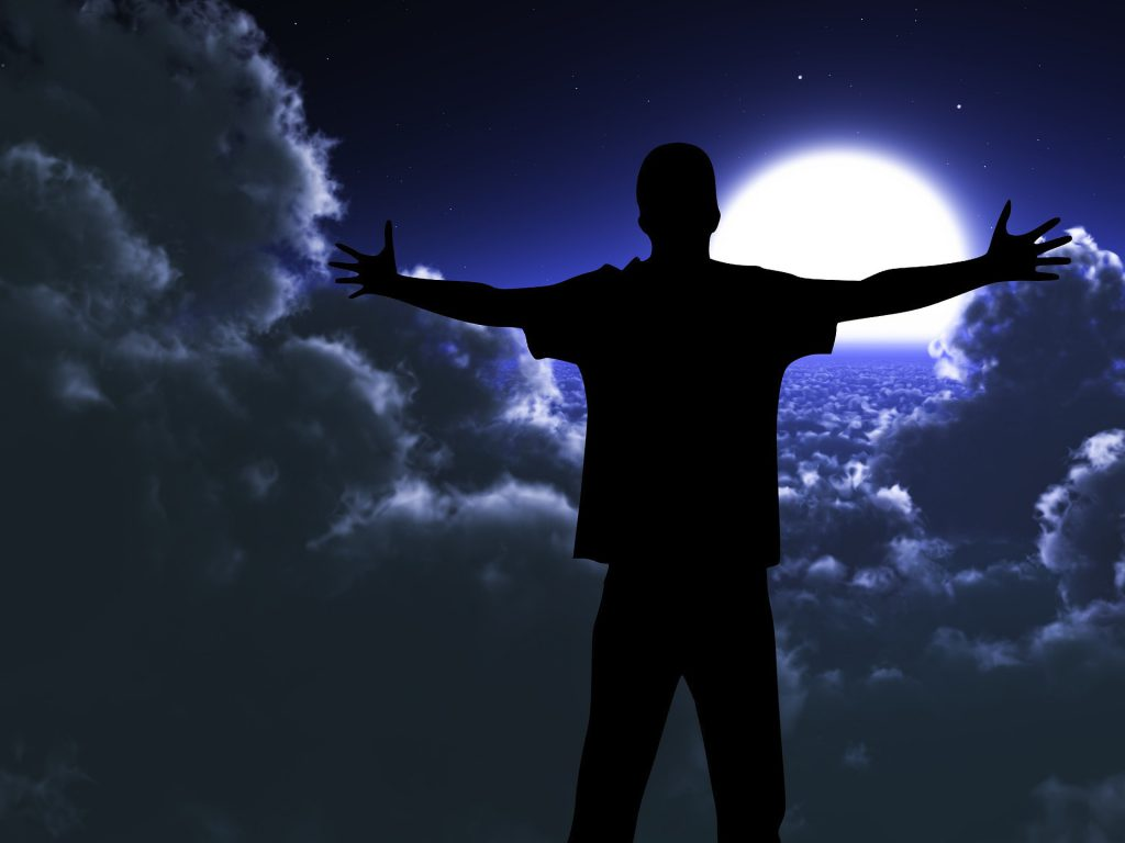 an image of a person praising God, arms outstretched.